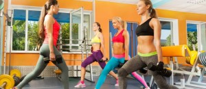 Group of women under guidance of fitness instructor exercise crossfit exercises with dumbbells and sit-downs